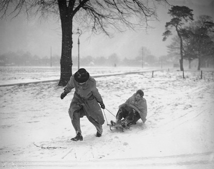 Man pulling boy on sled on Wimbledon Common, London, 19 December 1938.