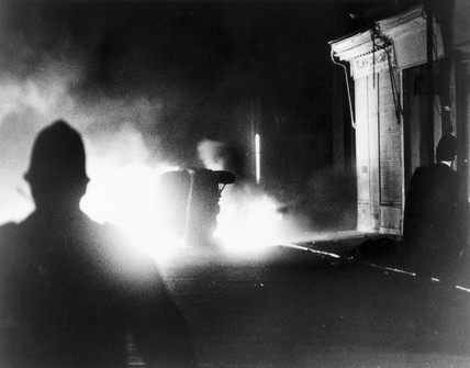 Police officers watching a car burning, London, April 1981.