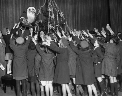 Father Christmas distributes toys to poor children, 7 December 1934.