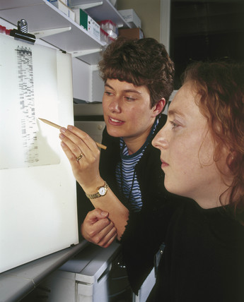Clinical molecular geneticists studying a radiograph of a DNA sequence, 2000.