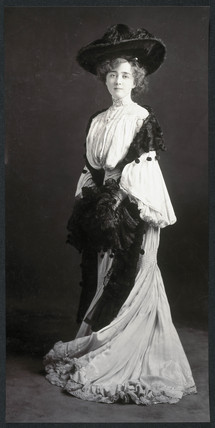 Young woman wearing an elaborate dres and hat, c 1900.