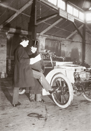 C S Rolls (left) and another man beside a motor car in a garage, c 1905.