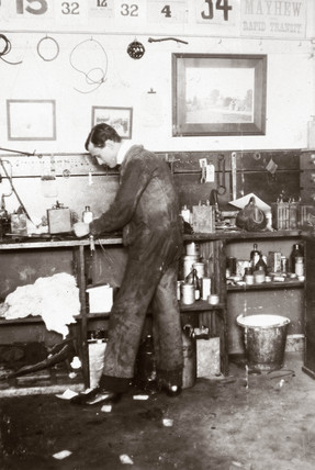 C S Rolls in overalls working in his garage, c 1900.