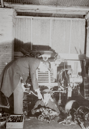 C S Rolls (standing) instructing a mechanic working in a garage, c 1900.