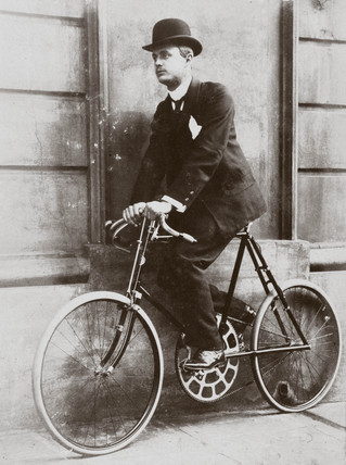 C S Rolls sitting on a bicycle 'geared to 180', c 1902.