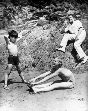 Two children exercising on a beach
