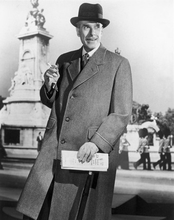 Smartly-dresed man in a long coat holding