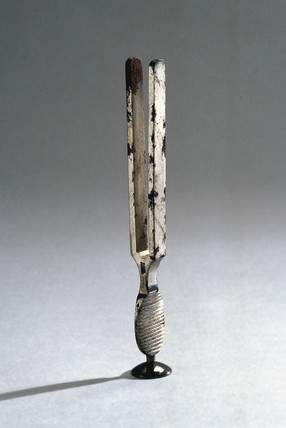 Steel tuning fork with oval grip and circular stand, c 1869-1874.