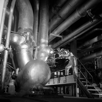 Worker with great pipes in powerhouse basement , ICI Wilton , 1955