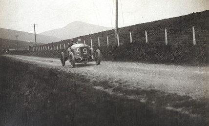 Racing car on a country road, c 1912.