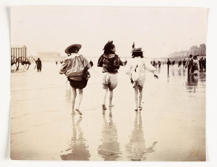 Three girls paddling at the beach, c 1890s.