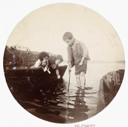 Small children playing at the waterside, c 1890s.