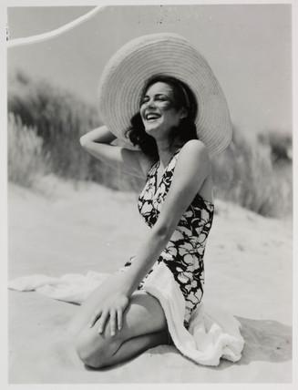 Woman on a beach in sunhat and swimsuit, c 1935.