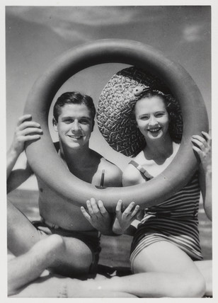 Man and woman looking through a rubber ring on beach, c 1935.
