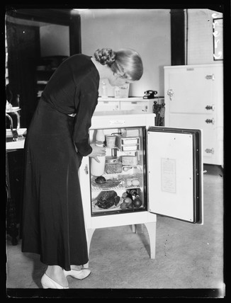 Woman taking milk from an electric refrigerator, 1933.