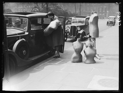 Unloading dresmaking dummies from a car, 1932.