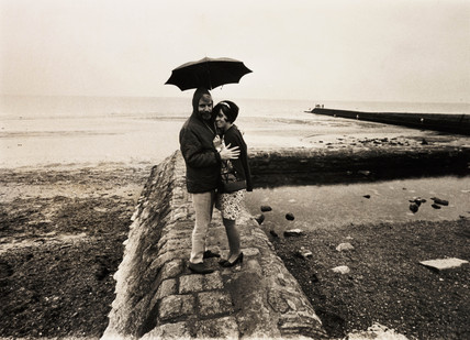 Couple sheltering under an umbrella, 1968.