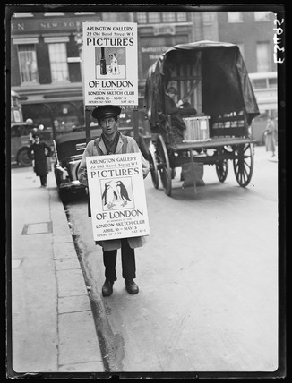 Man carrying a sandwich board, London, 1935.