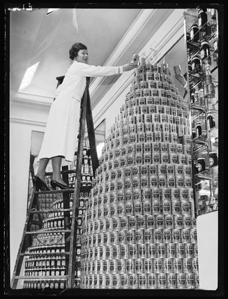 Shop asistant building giant tower of Heinz beans, c 1960s.