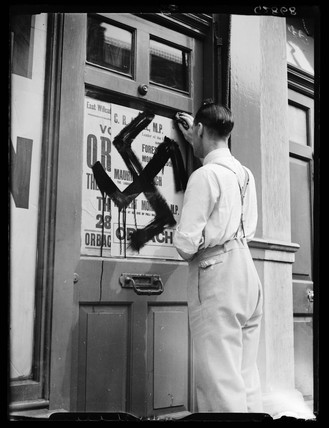 Removing swastika graffiti, 1938.