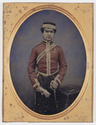 Soldier in ceremonial dress holding his sword, 19th century.