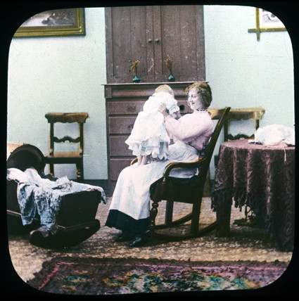 Woman and baby in rocking chair, c 1895.