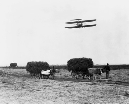 A Wright A biplane flying over farm workers at Pau, southern France, 1909.