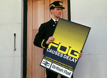 Station master with 'Fog' poster, April 1964.