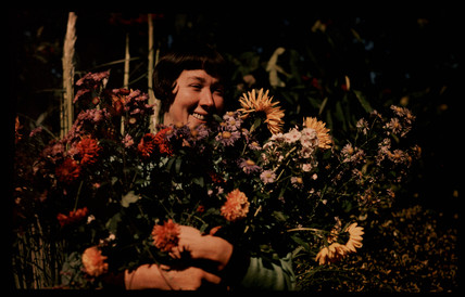 Woman holding flowers, c 1940.