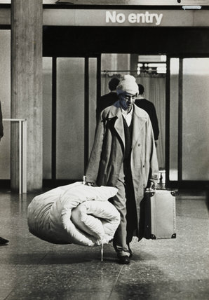 A Kenyan Asian migrant walks through customs at Heathrow, 1968.