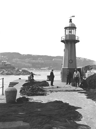 Fishermen mending nets by a lighthouse, St Ives, Cornwall, c 1920.
