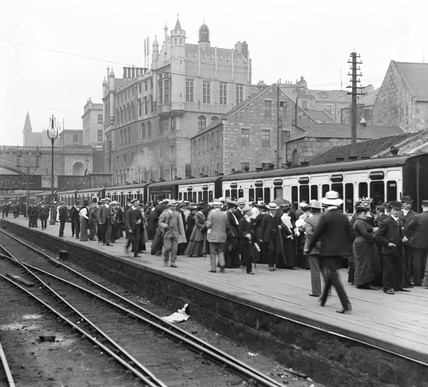 Passengers at a railway station, c 1905.