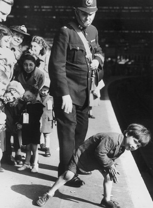 Policeman with evacuees at a London railway station, 28 September 1940.