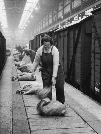 Female worker unloading a sack onto a conveyer belt, c 1950s?