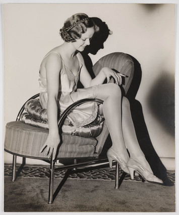 Woman in underwear sitting in a chair, 1936.