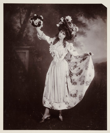 Studio portrait of a woman holding flowers, c 1900s.