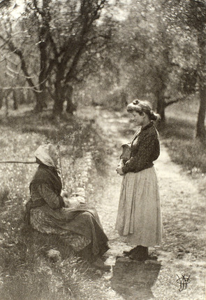 Two women talking on a country lane, c 1905.