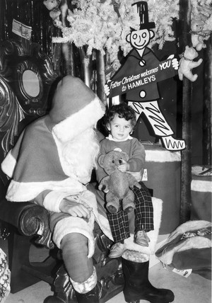 Child sitting on Father Christmas' knee, Hamleys toy shop, London, 1986.