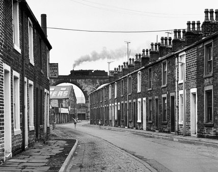 Steam train crossing a viaduct over a terraced street, Lancashire, 7 July 1968.