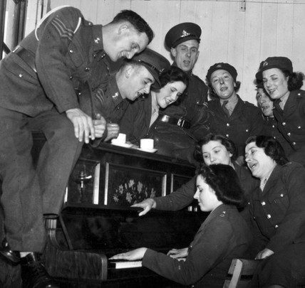 Soldiers and ATS girls at the piano, Fort Crosby, March 1940.