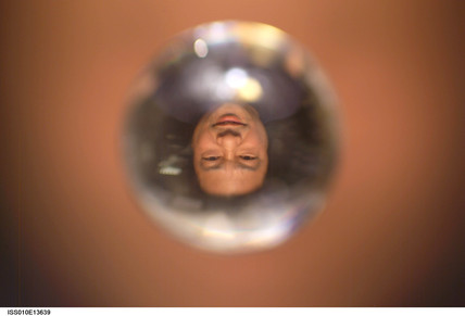 Commander Leroy Chiao's face in a water droplet in space, 2005.
