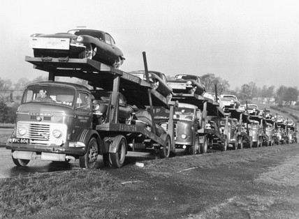 'E' type Jaguar motor cars being delivered
