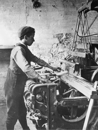 Young boy working in a cotton mill, c 1880s.