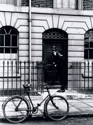 Postman delivering a telegram to an addres in London, c 1930s.