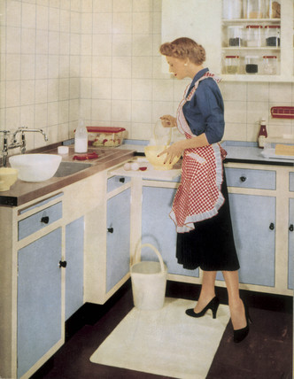Woman in a fitted kitchen, 1955.
