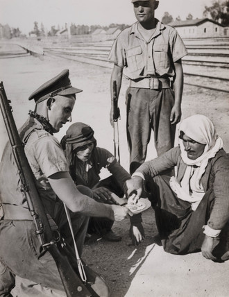 British soldiers sharing rations with prisoners, Jerusalem, 1938.