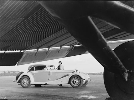 Mercedes-Benz convertible under the wing of a Junkers plane, 1930s.