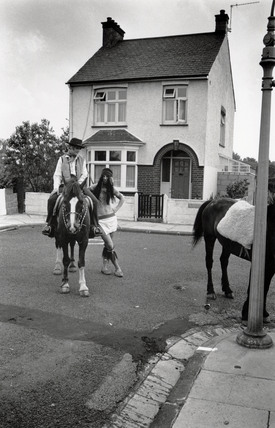Woman (astride a horse) with man, both wearing fancy dress, 1968.