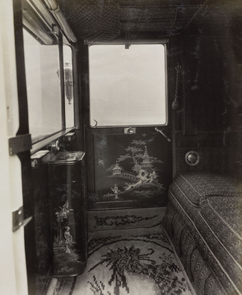 Car interior showing elaborate design and luxurious upholstery influenced by Chinese design