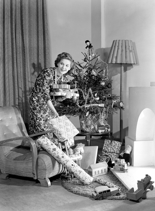 Woman putting Christmas presents under a tree, c 1950.